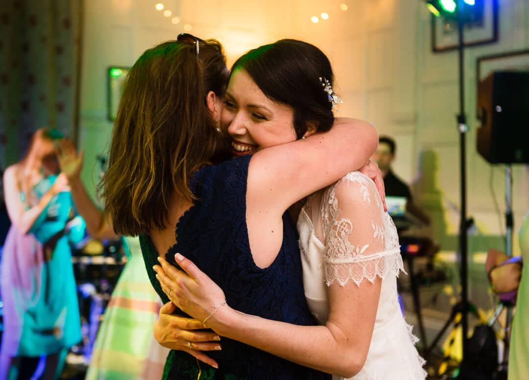 Bride hugging wedding guest