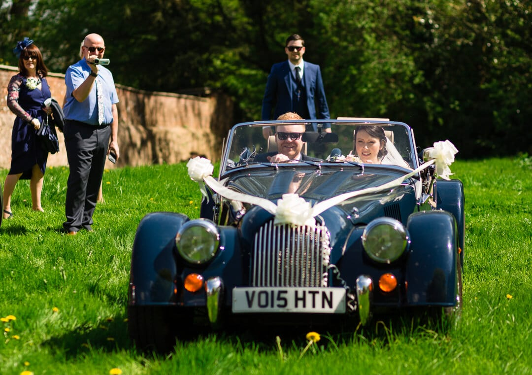 Bride and groom driving away in blue Morgan at Homme House wedding
