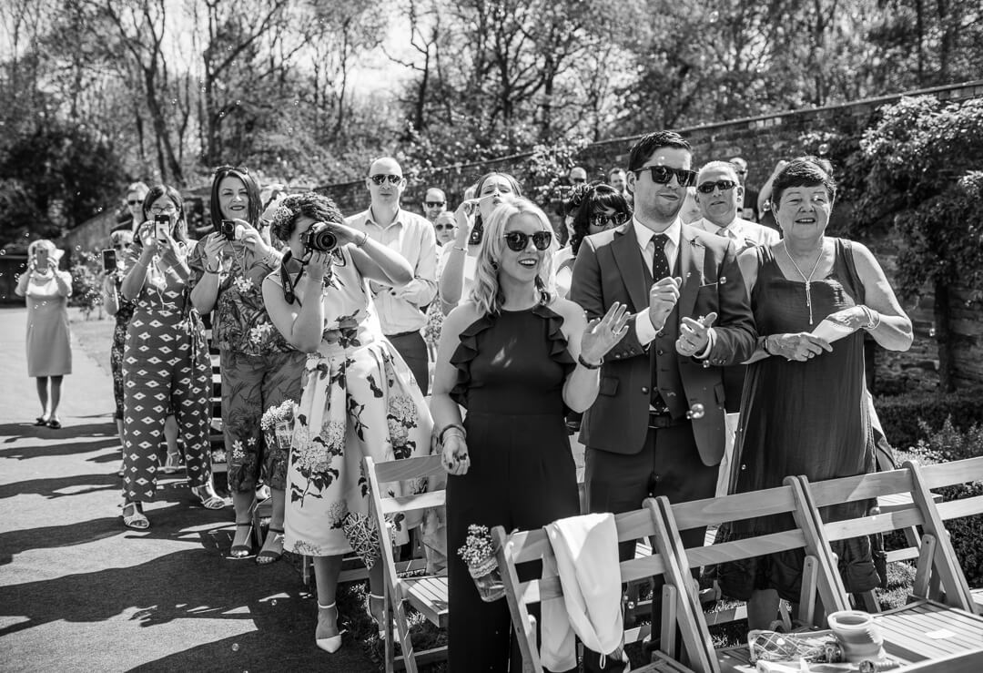 Documentary wedding photo of guests cheering at ceremony
