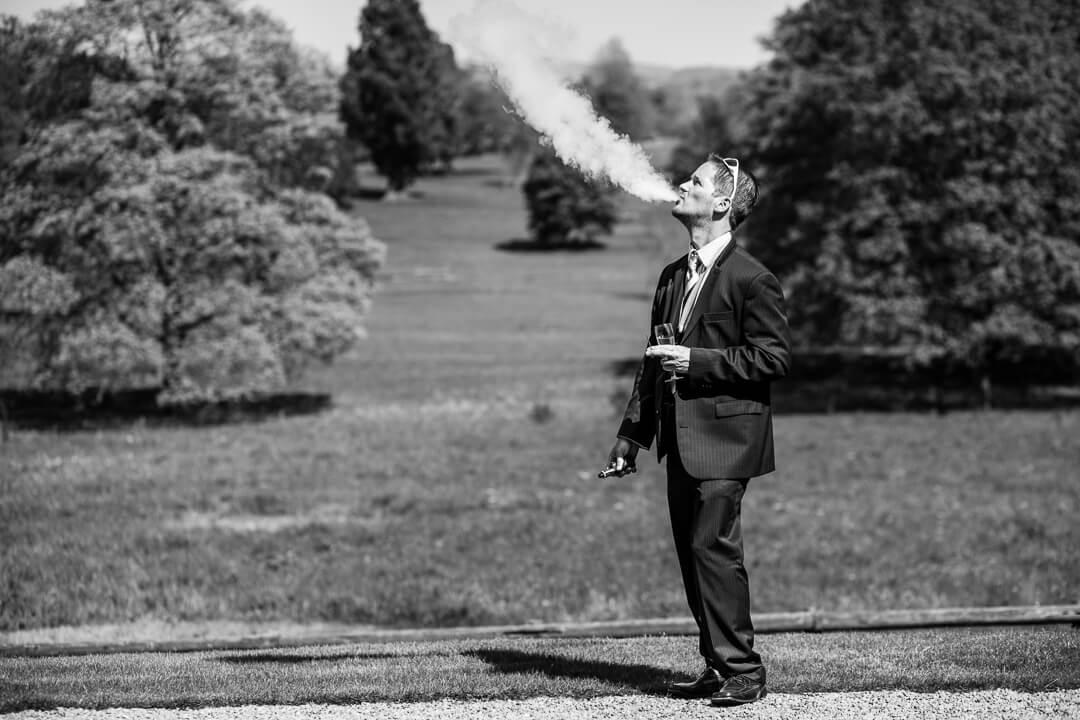 Documentary wedding photo of guest smoking e cigerette