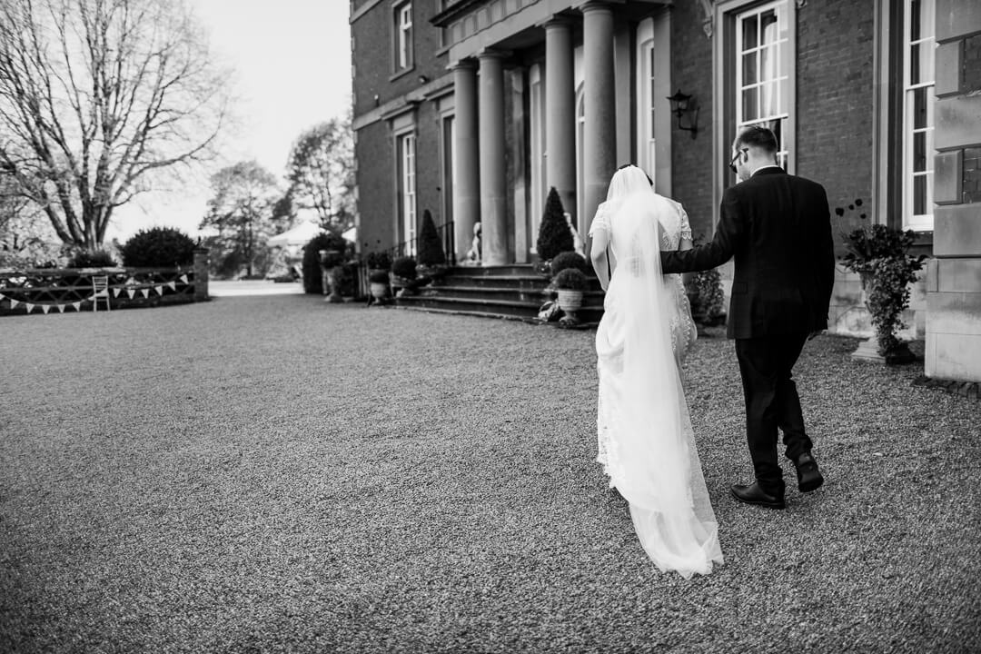 Bride and groom walking in front of venue at Homme House wedding