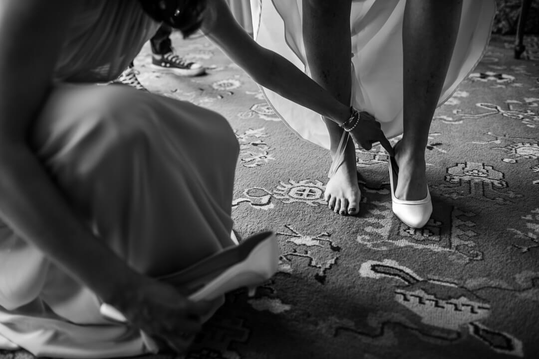 Natural wedding photo of bride putting on shoes