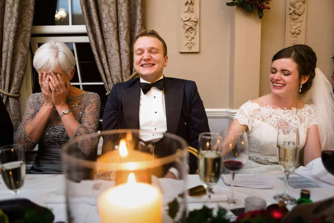 Bride and groom reacting to wedding speeches