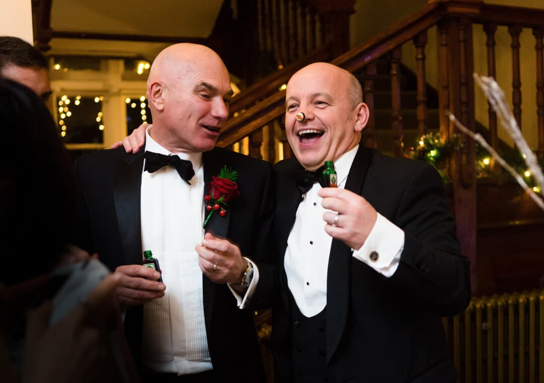 Grooms father laughing at wedding