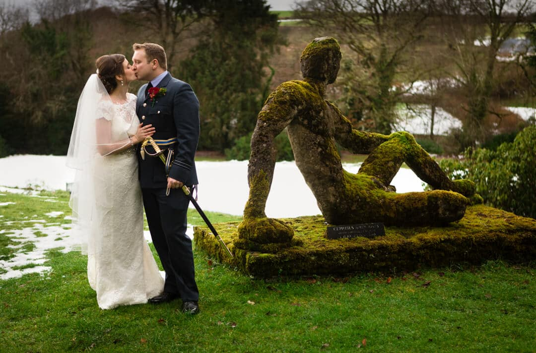 Bride and groom kissing in garden at Welsh winter Wedding