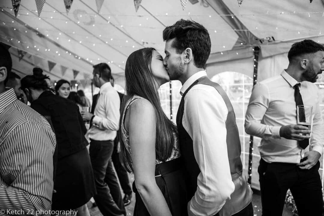 Wedding guests kissing on the dance floor at marquee wedding