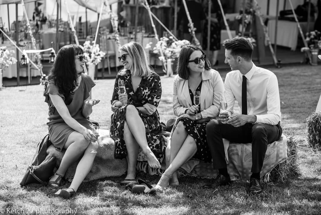 Documentary wedding photo of guests sitting on straw bale