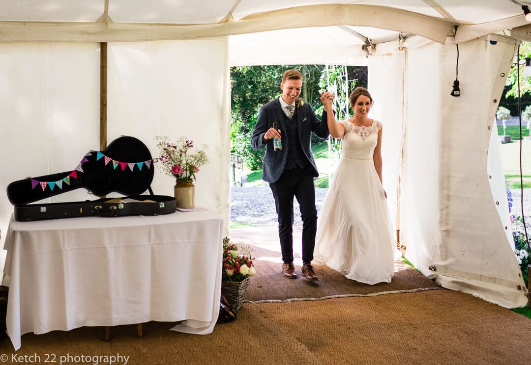 Bride and groom make an entrance at Marquee wedding
