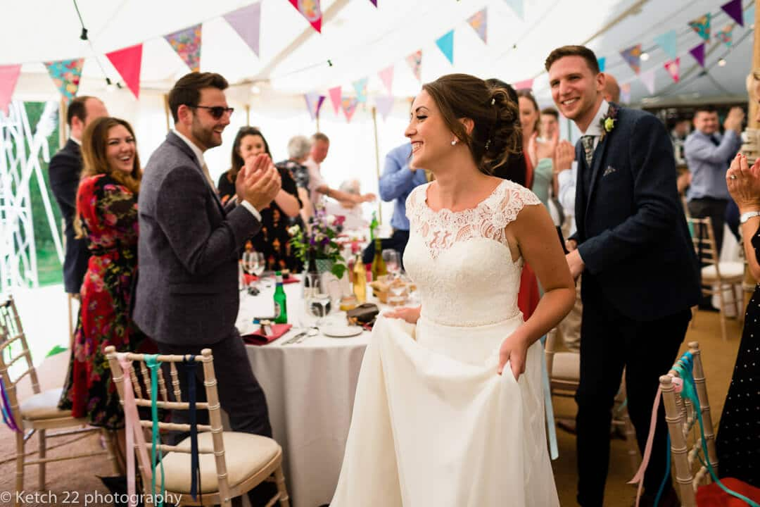 Wedding guests cheering bride and groom in Marquee