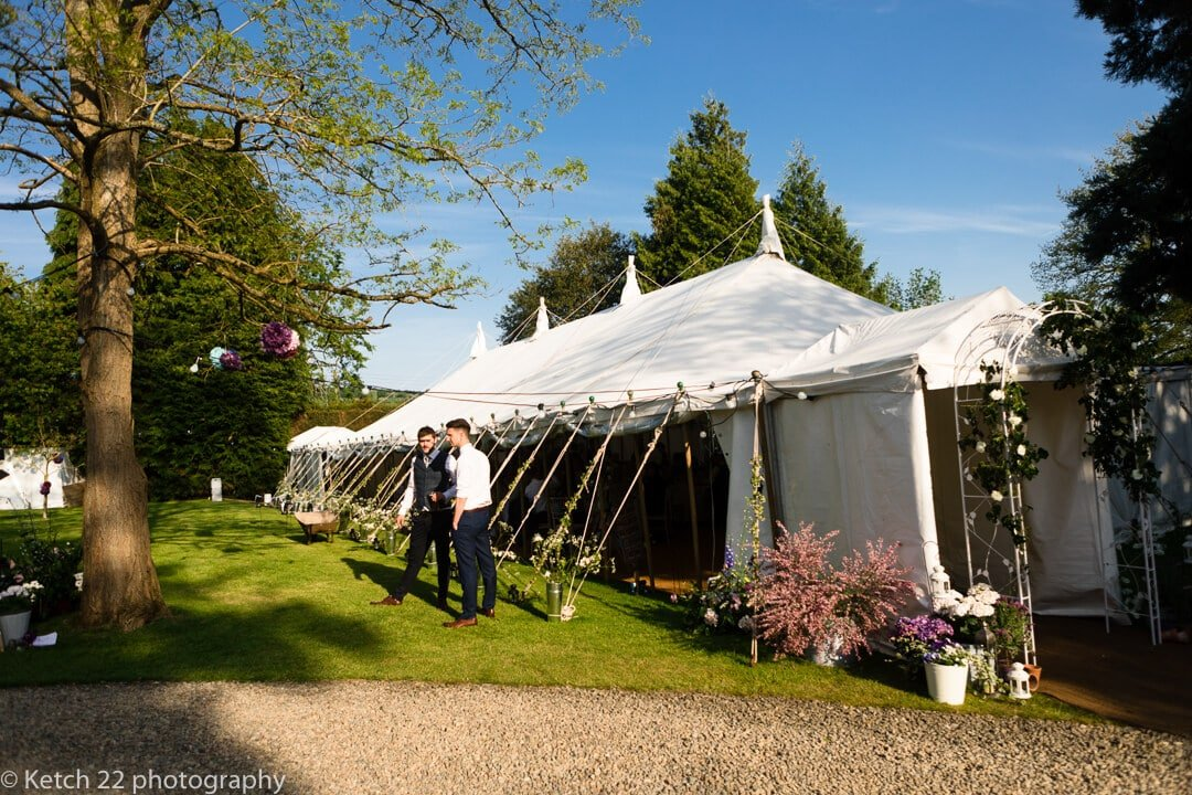 Guests standing outside wedding marquee on sunny evening