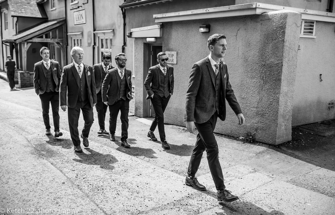 Groom and ushers walking in front of Lion Hotel in Herefordshire at Marquee wedding