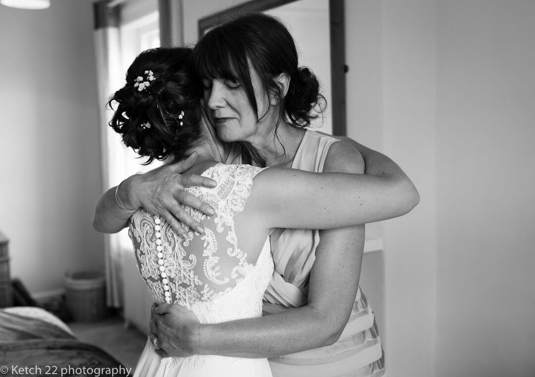 Bride hugging her mother at wedding preparations