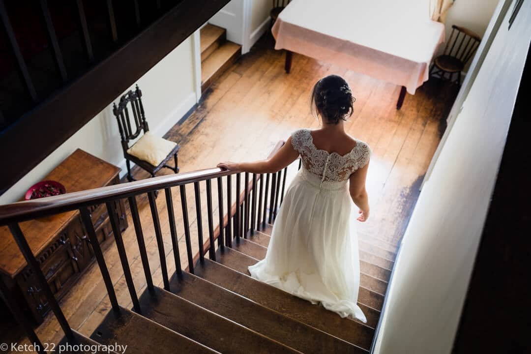 Bride descending stairs at wedding