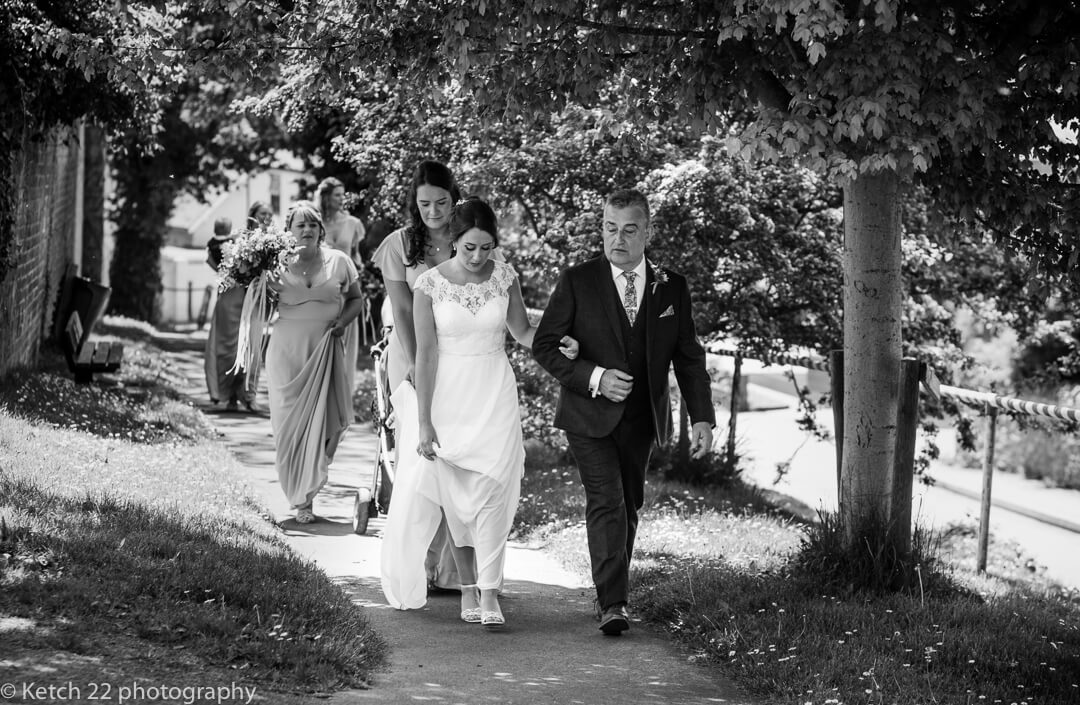 Bride and father walking to the Church at Marquee wedding