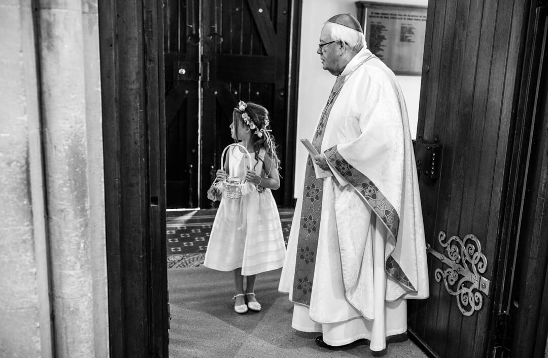 Priest and flower girl waiting for bride