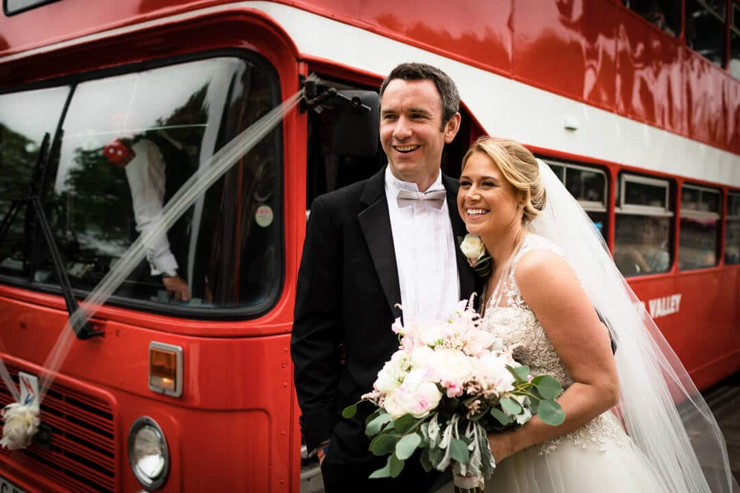Bride and groom in front of red double decker bus