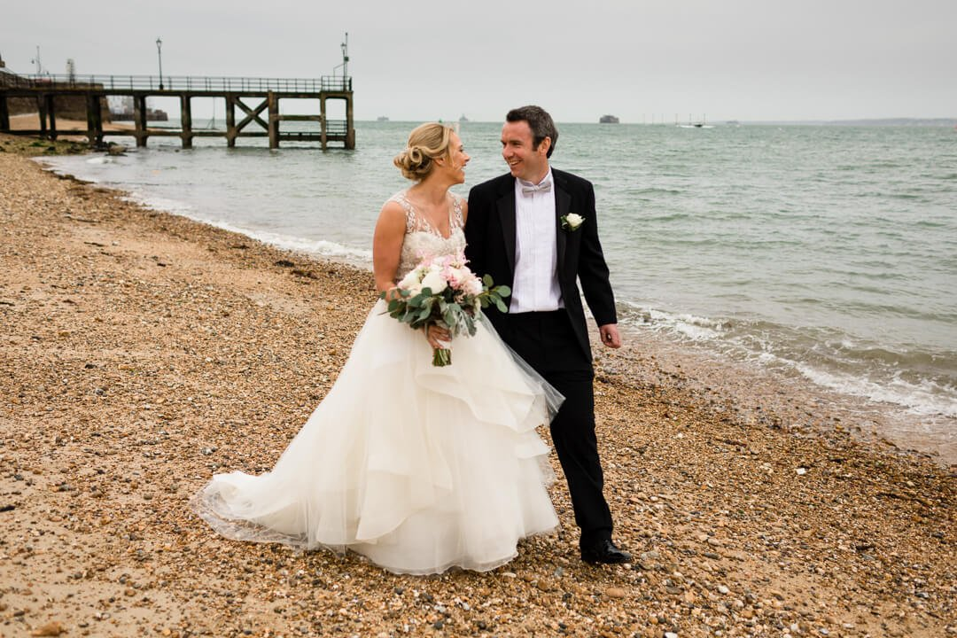 Bride and groom walking on beach at Portsmouth wedding
