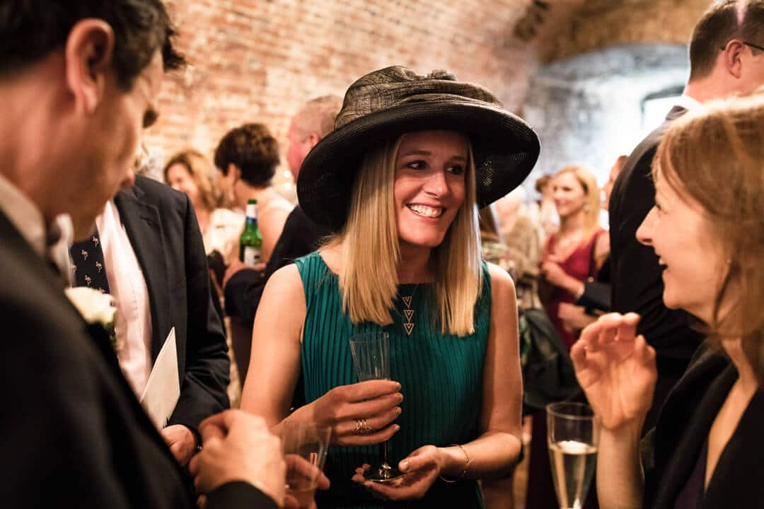 Wedding guest wearing black hat and green dress at reception