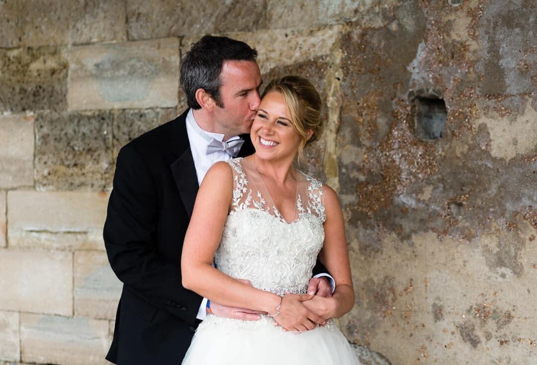 Groom kissing bride by old sea wall