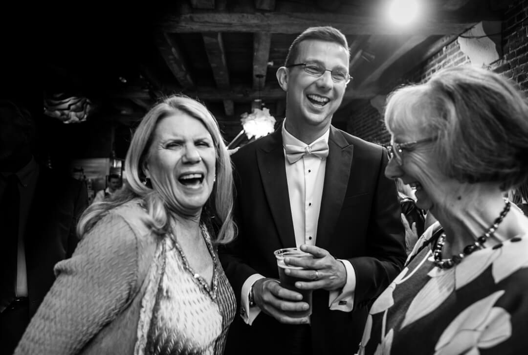 Best man laughing and chatting at Wedding reception