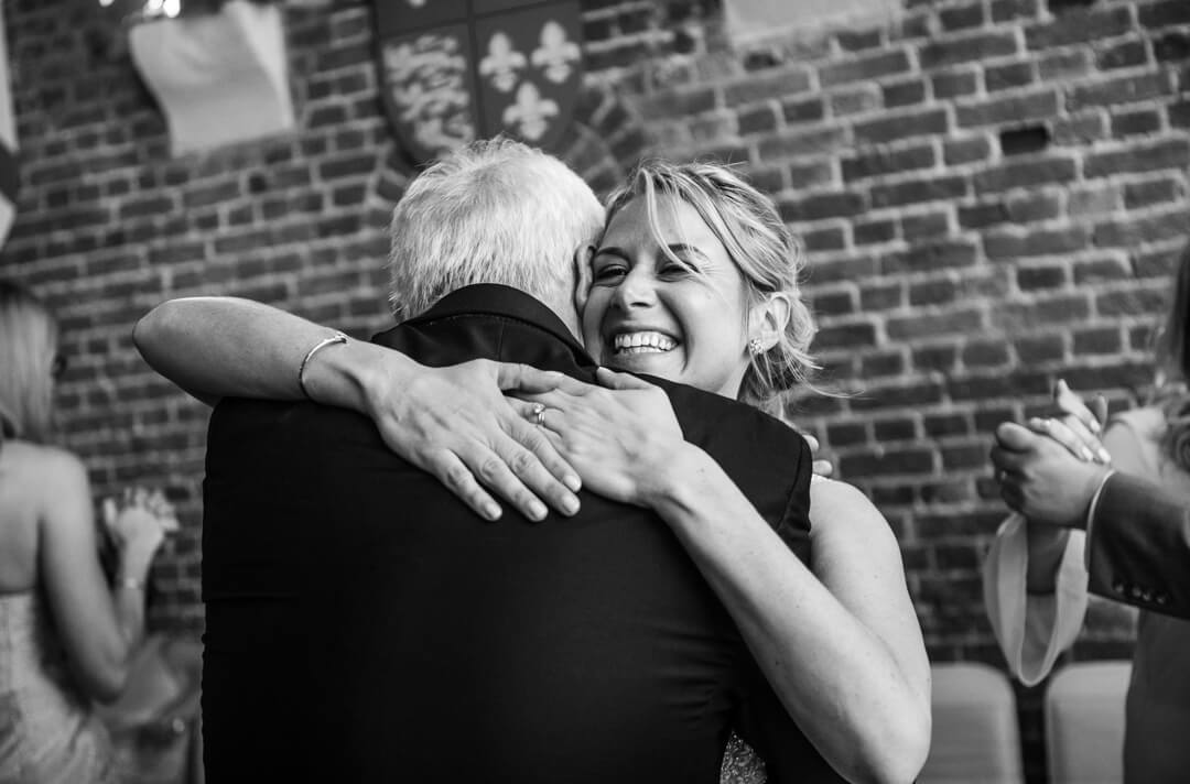 Bride hugging father at wedding reception