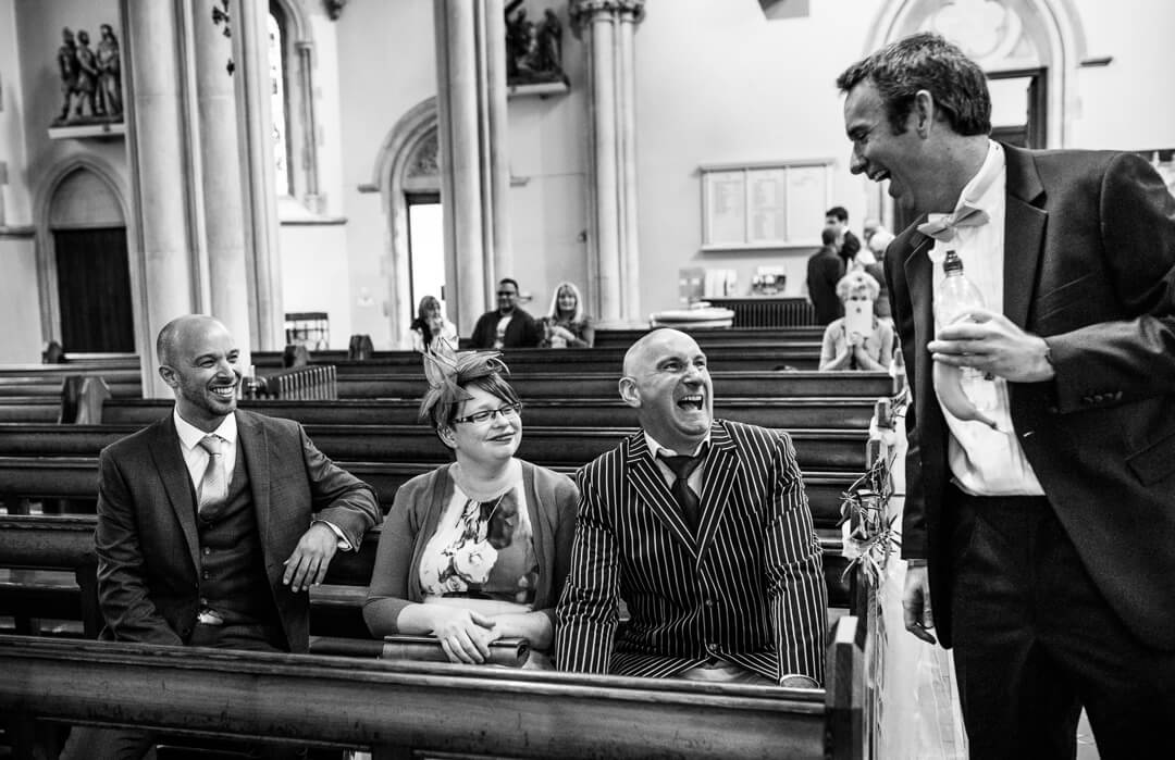 Groom greeting wedding guests in Church