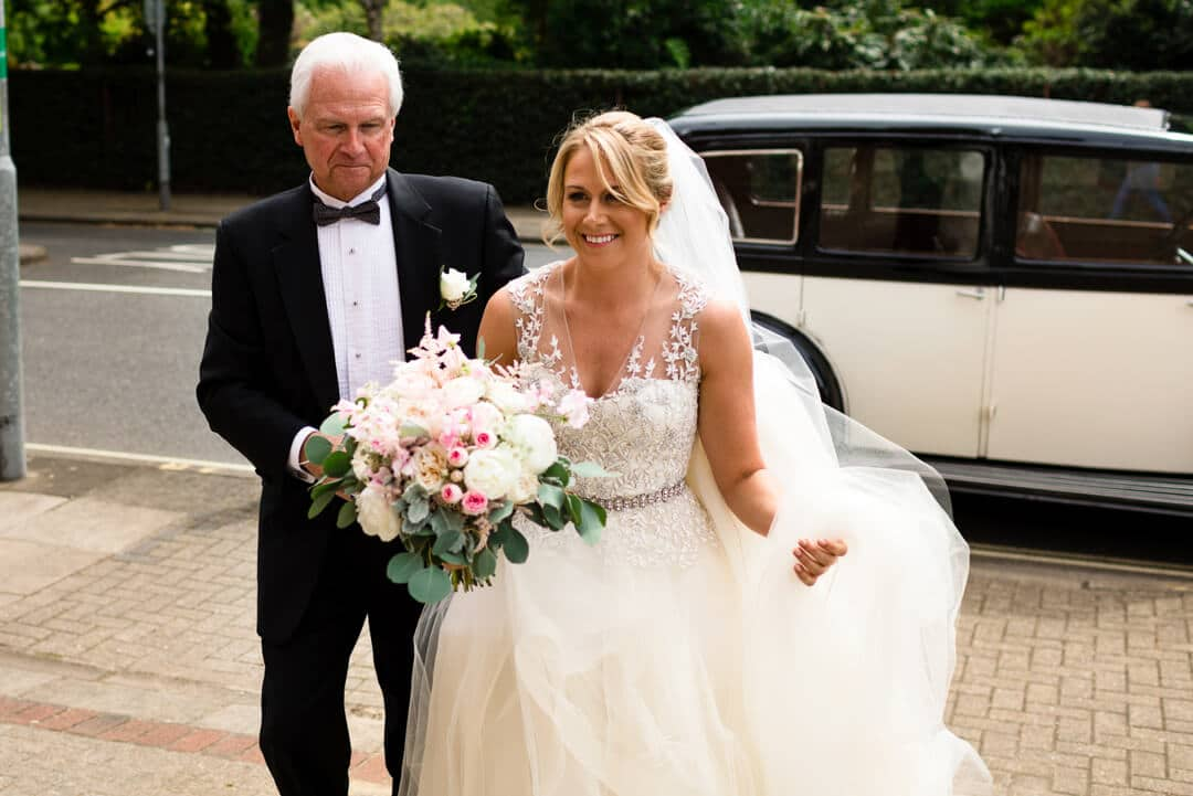 Bride and father walking from wedding car