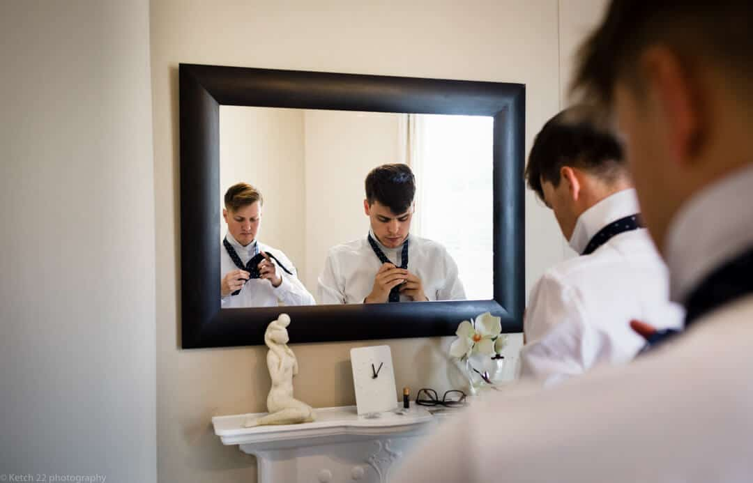 Wedding preparation photography with groom putting tie on in mirror