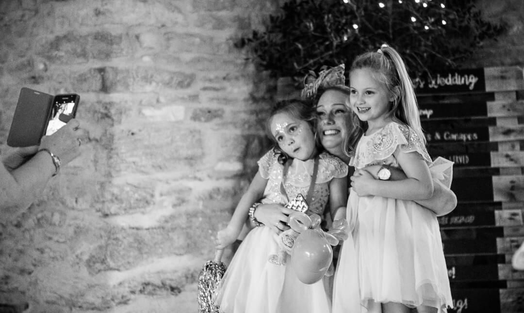 Flower girls posing for camera at Cotswold wedding
