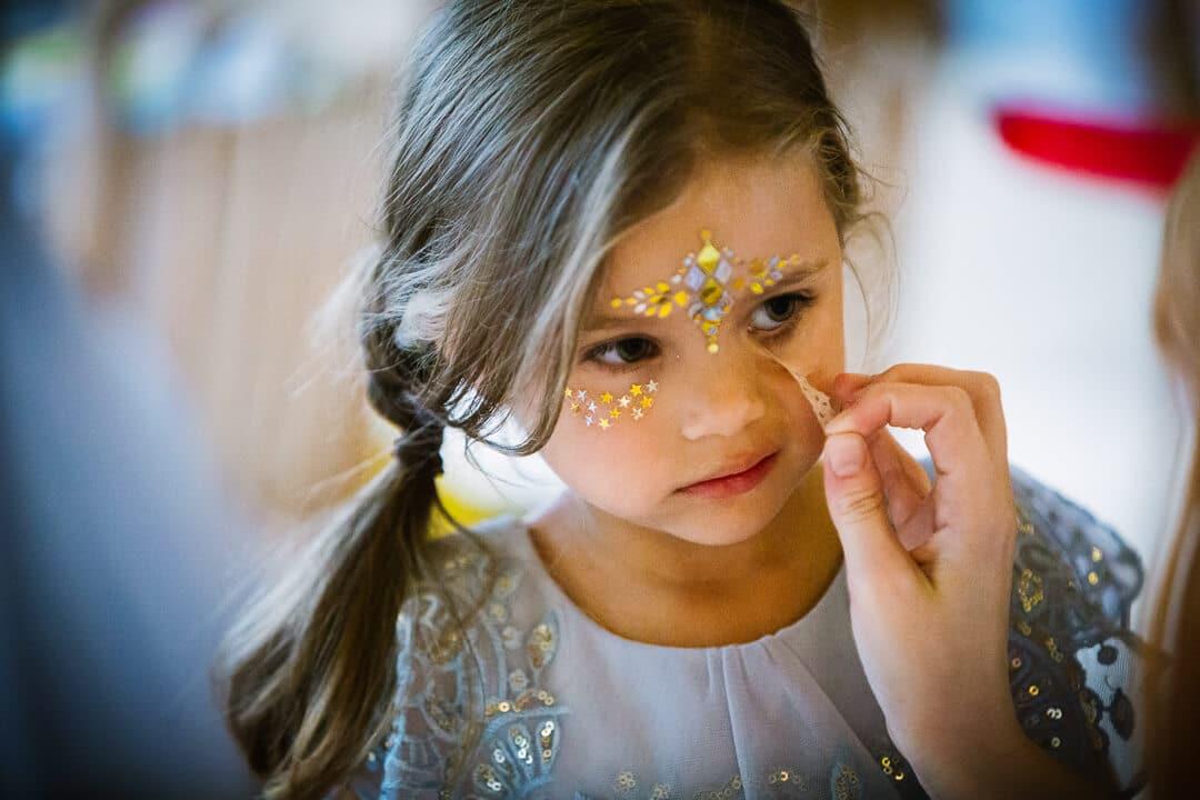 Flower girl having her face painted at Kingscote Barn Wedding