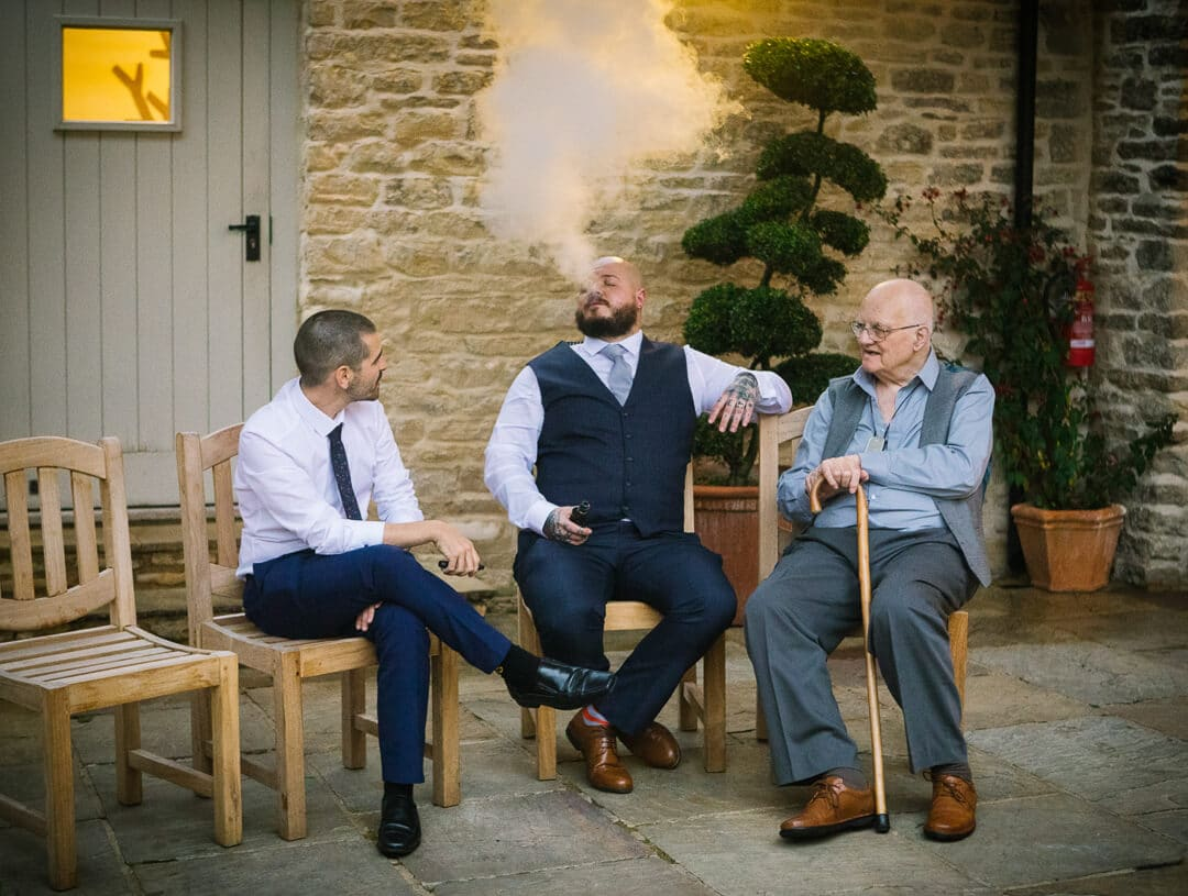 Wedding guest blowing vape into the air at Kingscote Barn