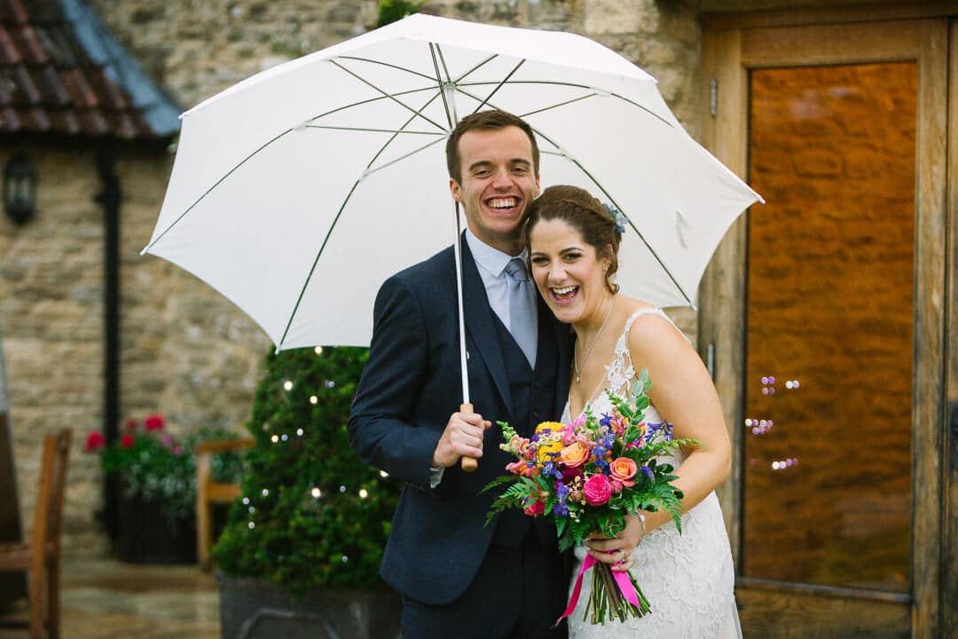 Portrait of bride and groom with umbrella at Kingscote Barn wedding