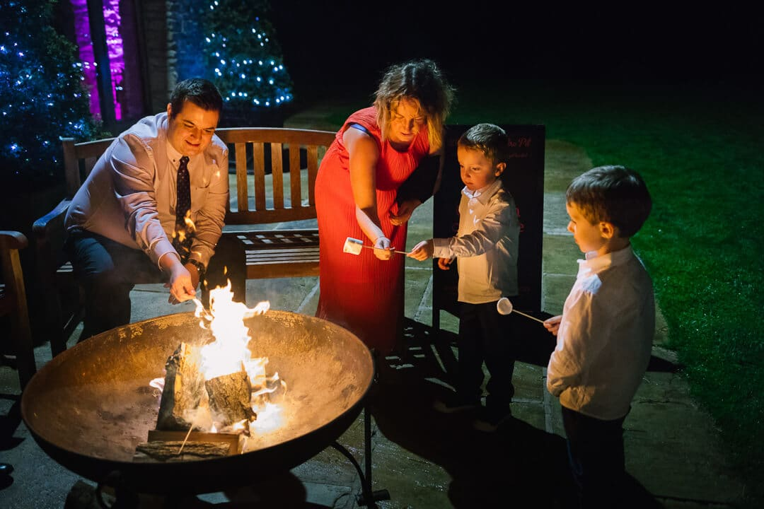 Guests toast marsh mellows over a fire at Kingscote Barn Wedding