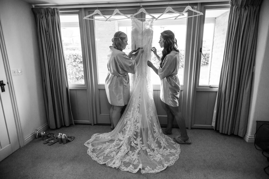 Natural wedding photo of bridesmaids getting wedding dress ready