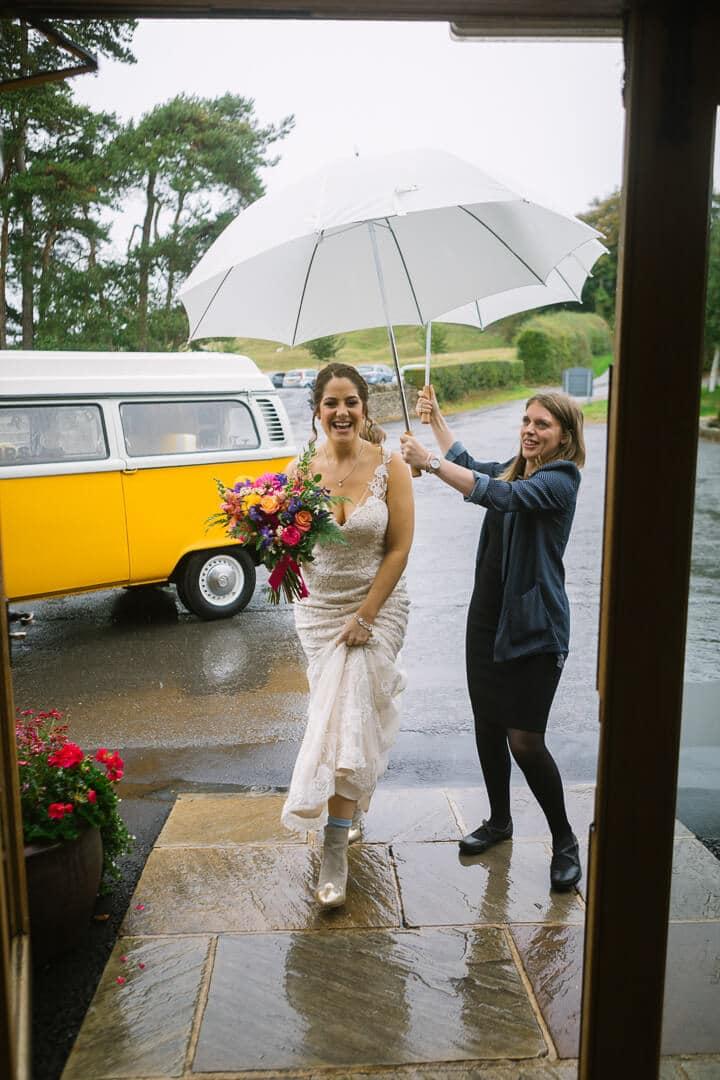 Bride arrives at Kingscote Barn wedding in the rain