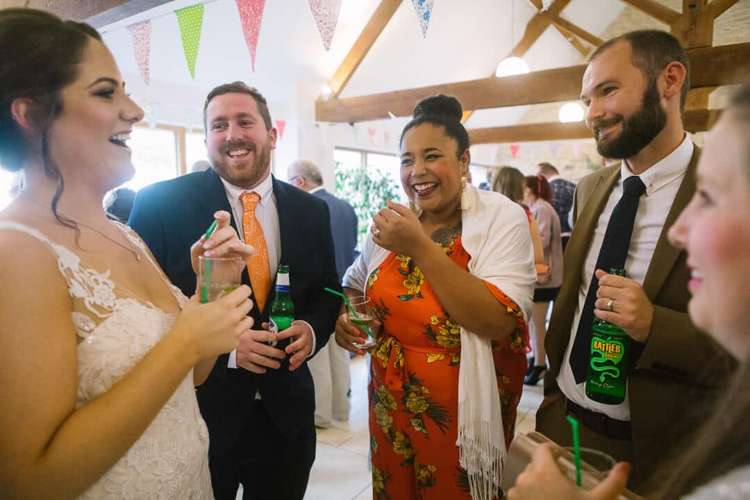 Wedding guests laughing with bride at Gloucestershire Wedding