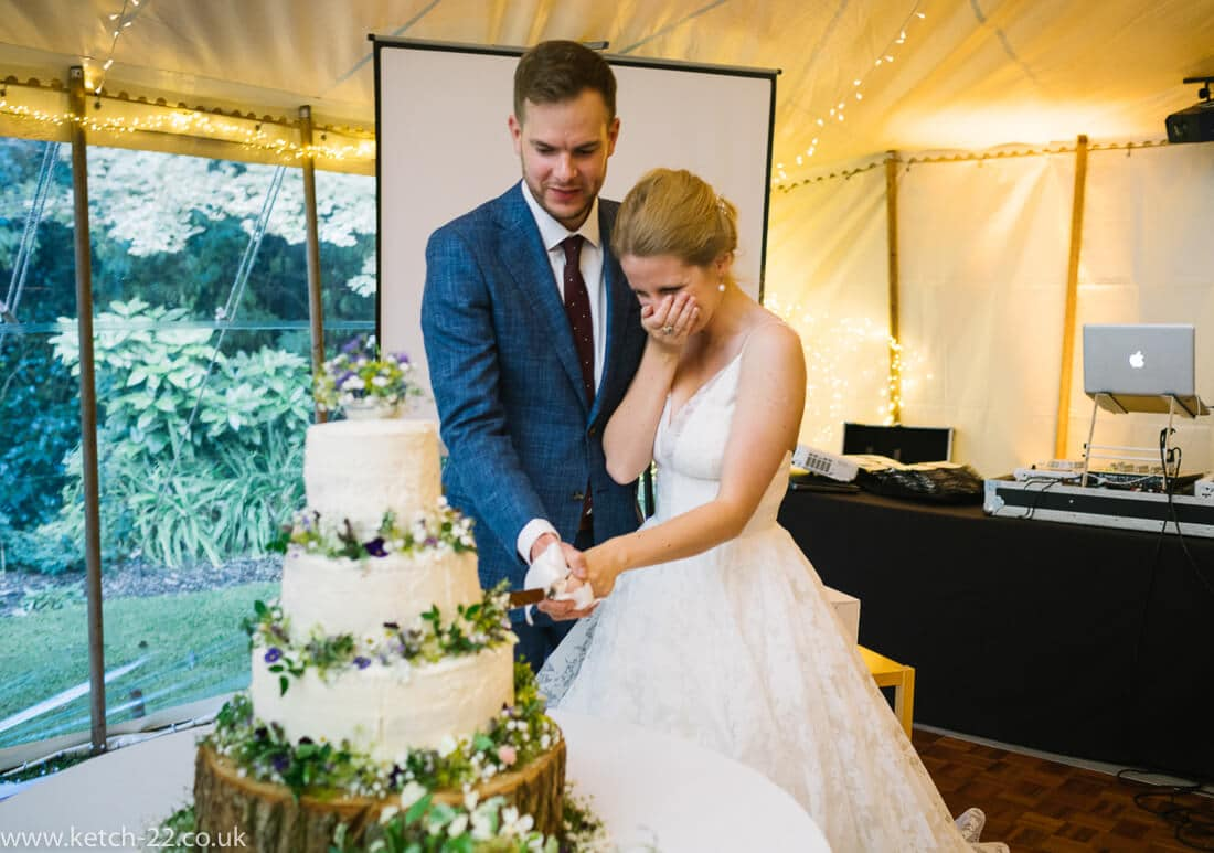 Bride and groom cutting large white wedding cake