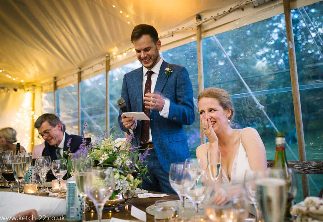Bride laughing at grooms wedding speech