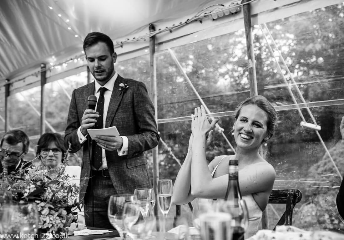 Bride applauding grooms wedding speech