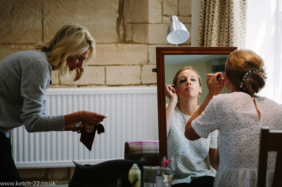 Bride putting on make up in front of mirror at wedding