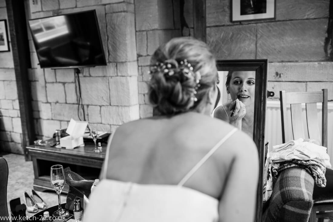 Bride putting on lip stick in mirror - Winchcombe wedding photographer