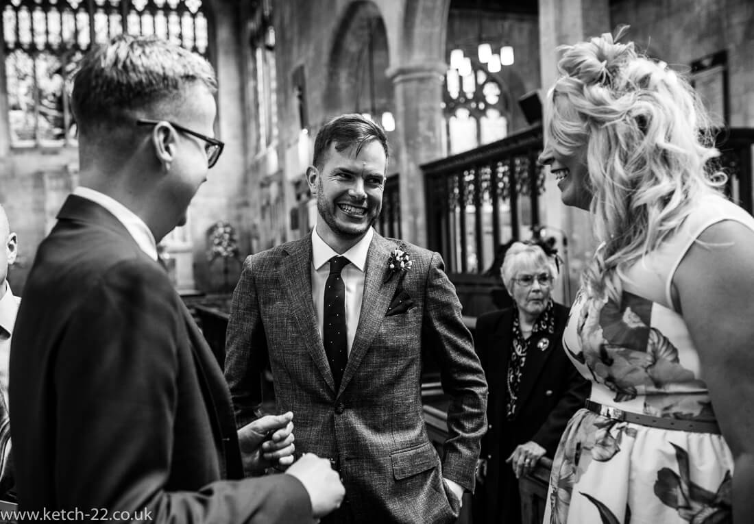Groom laughing and greeting wedding guests