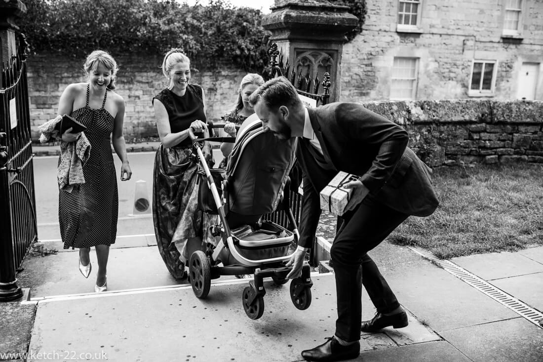Groomsmen helping wedding guest with pram