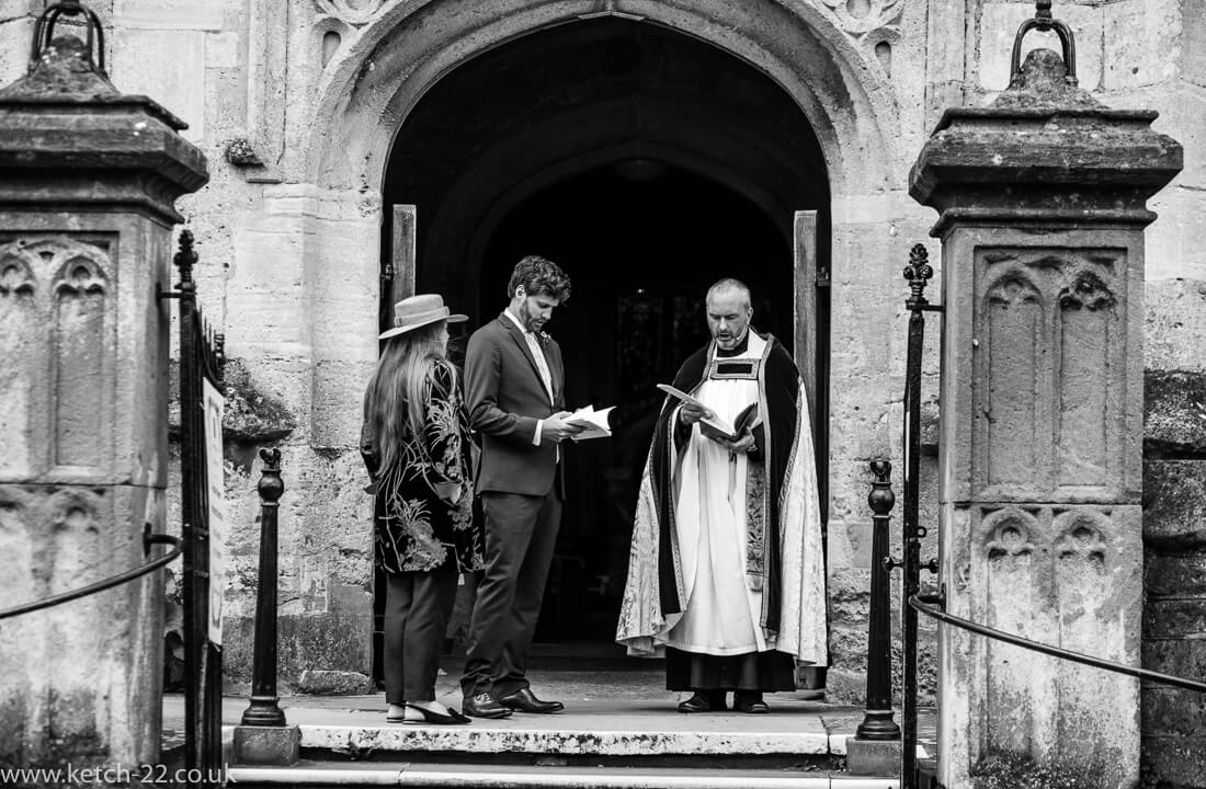 Vicar and grooms men waiting for bride