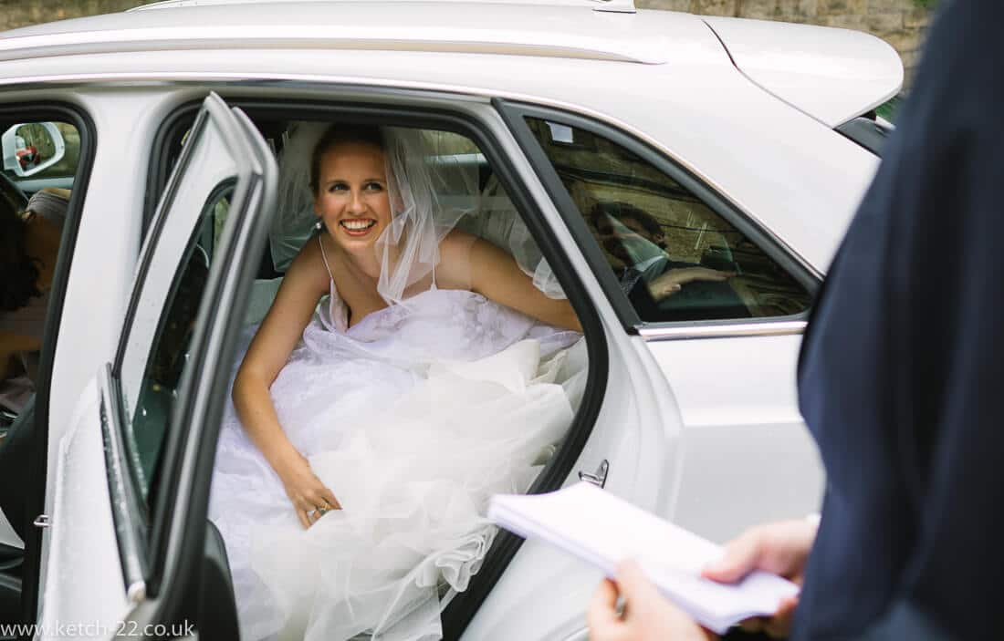 Bride getting out of white wedding car
