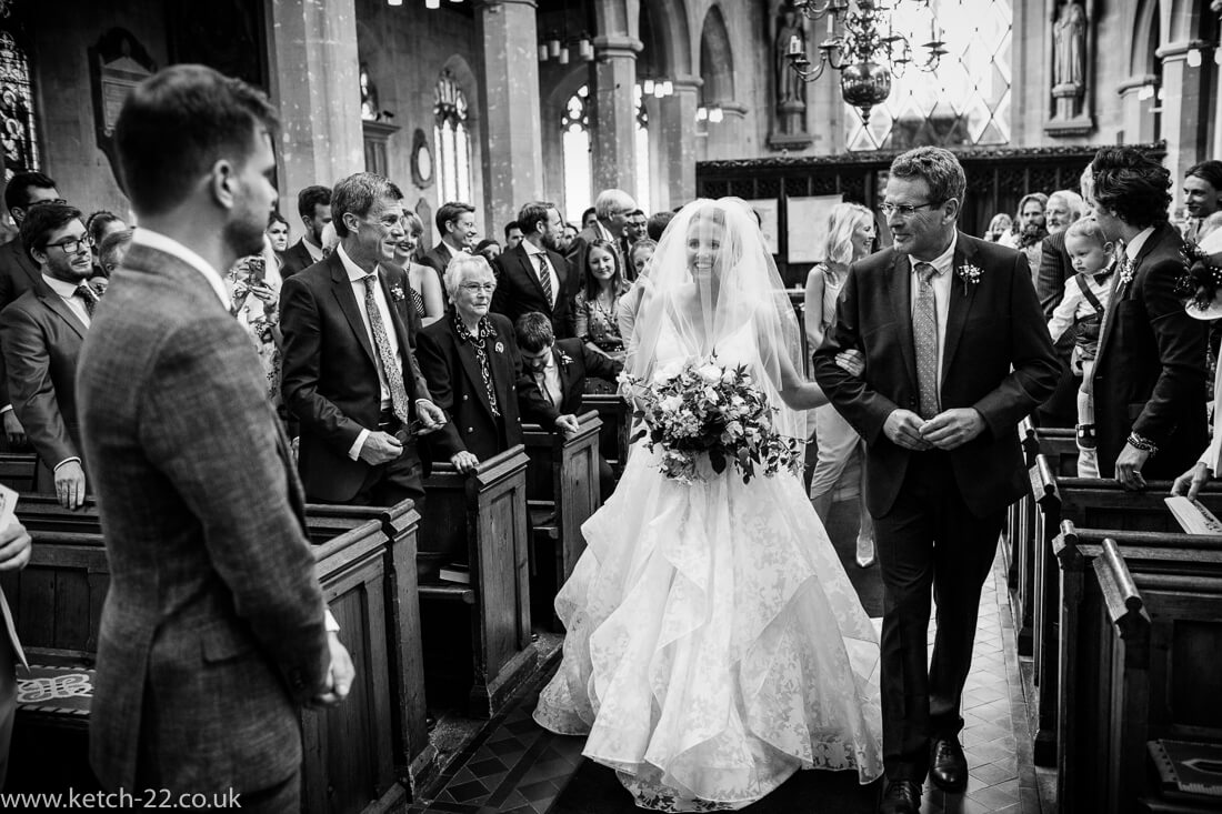 Bride looking at groom at she enters church wedding ceremony