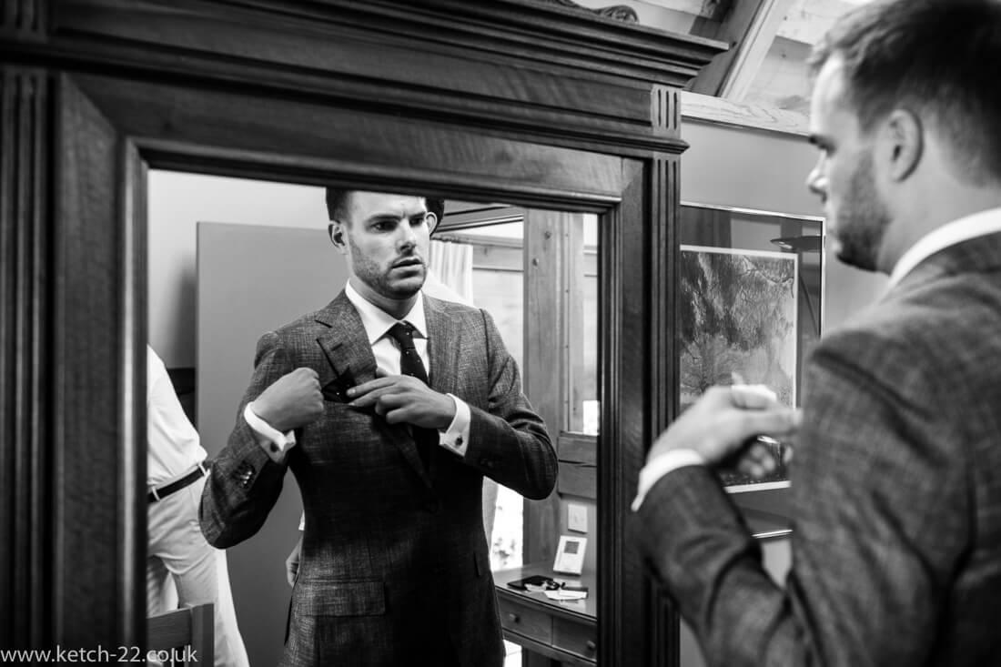 Groom looking into mirror at Winchcombe wedding preparations