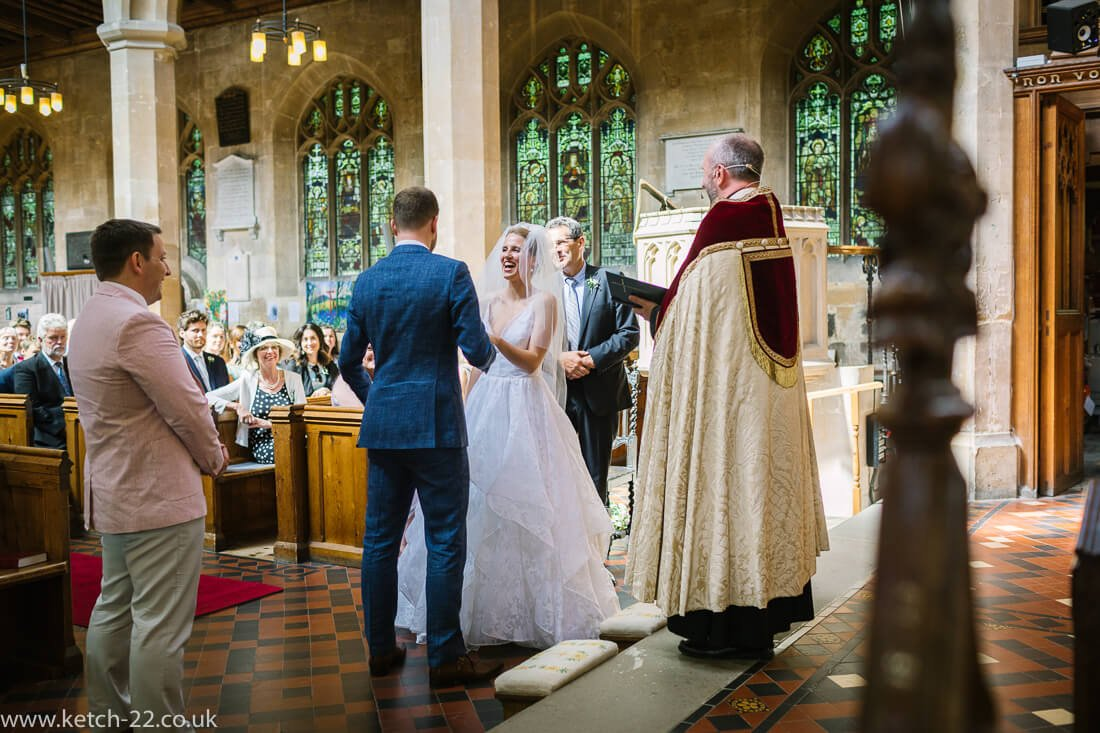 Reportage wedding photo of bride putting ring on groom