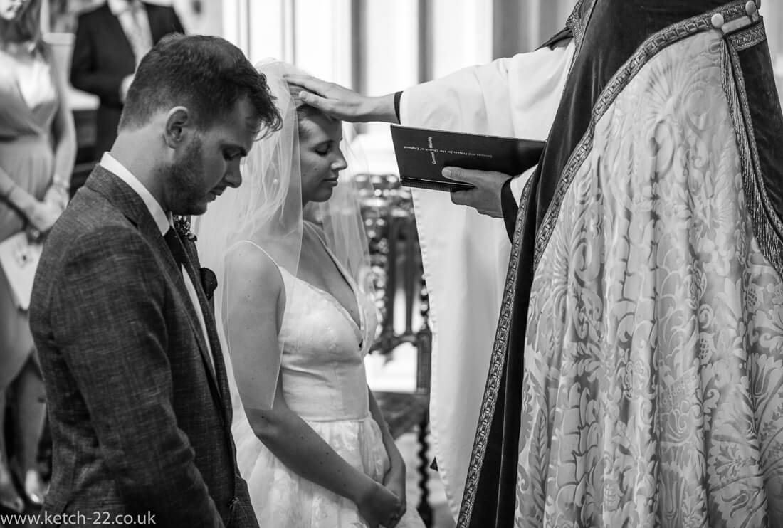 Vicar blessing bride and groom at Gloucestershire wedding