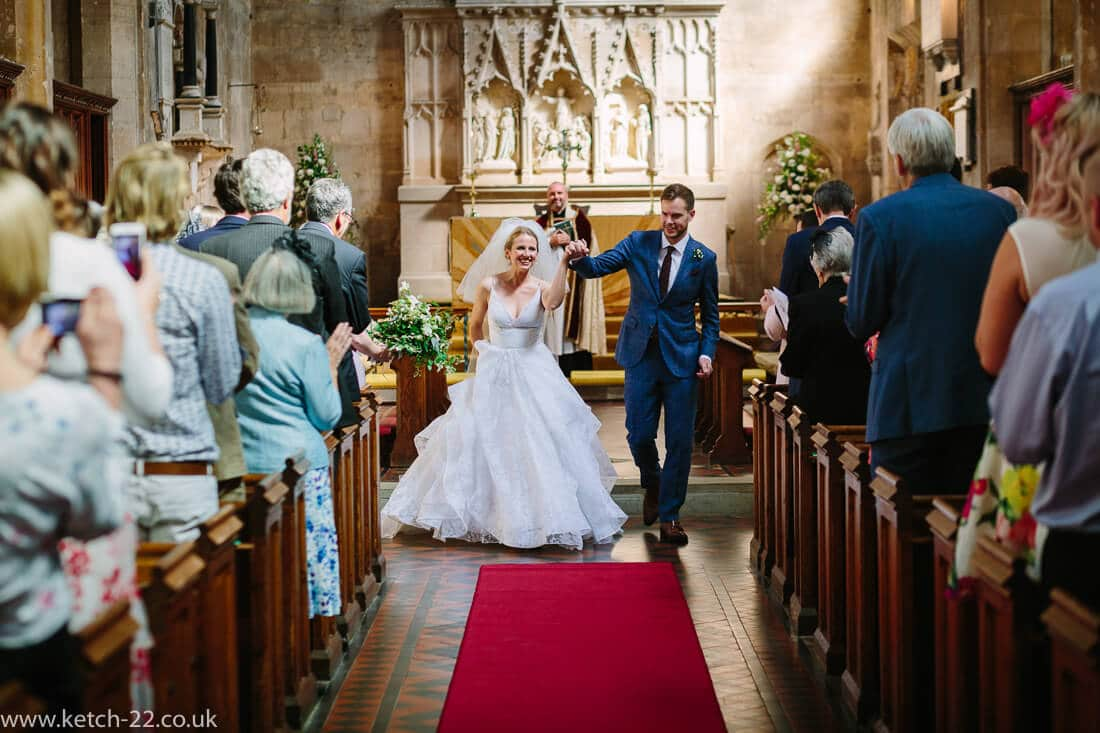 Bride and groom celebrate as they leave wedding ceremony